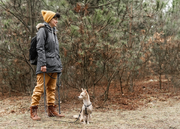 Tiro completo de mulher com cachorro na floresta