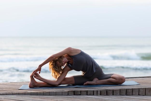Tiro completo de mulher praticando ioga no tapete perto do mar