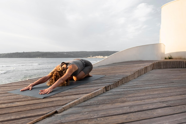 Tiro completo de mulher praticando pose de ioga ao ar livre no tapete