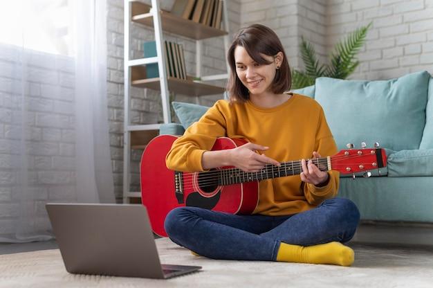 Tiro completo de mulher tocando guitarra com laptop