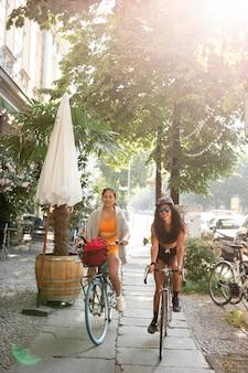 Tiro completo de mulheres andando de bicicleta