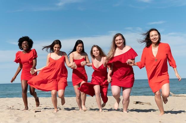 Tiro completo de mulheres correndo na praia