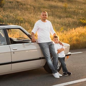 Tiro completo de pai e filho posando com o carro