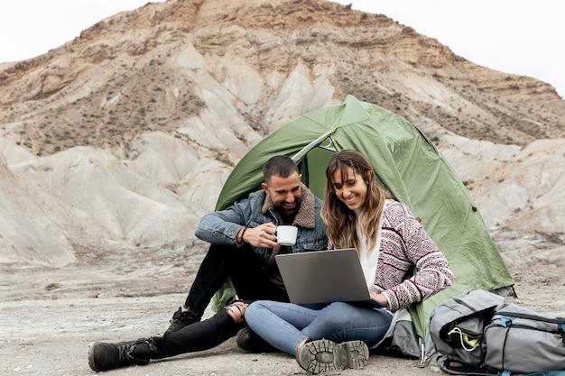 Tiro completo de pessoas com laptop e xícara de café