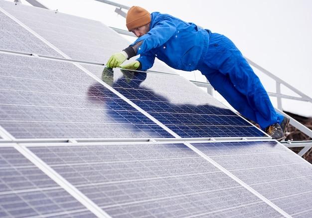 Tiro completo do comprimento de um trabalhador profissional do eletricista do engenheiro que instala ou repara os painéis solares no trabalho fotovoltaico do trabalho da ocupação da profissão da substituição do copyspace da energia renovável.