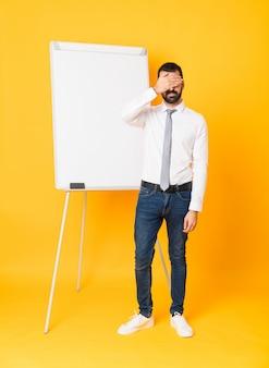 Tiro completo do empresário dando uma apresentação no quadro branco sobre olhos de cobertura amarela pelas mãos. não quero ver algo