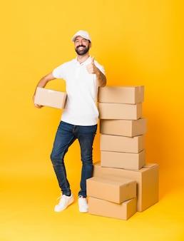Tiro completo do entregador entre caixas sobre amarelo isolado com polegares para cima, porque algo de bom aconteceu