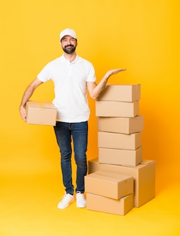 Tiro completo do entregador entre caixas sobre amarelo isolado segurando copyspace imaginário na palma da mão para inserir um anúncio