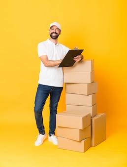 Tiro completo do entregador entre caixas sobre amarelo isolado