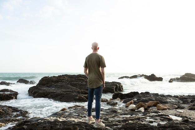 Tiro completo do homem de pé nas rochas