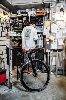 Tiro completo do homem na loja de bicicletas