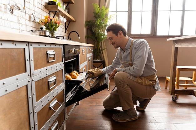 Tiro completo do homem segurando a bandeja com croissants