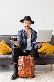 Tiro completo do homem segurando a câmera e o laptop