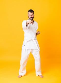 Tiro completo do homem sobre amarelo isolado fazendo karatê