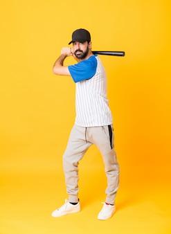 Tiro completo do homem sobre amarelo isolado jogando beisebol