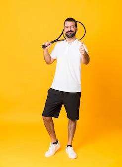 Tiro completo do homem sobre amarelo isolado jogando tênis e com o polegar para cima