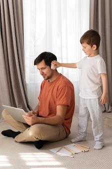 Tiro completo do homem trabalhando no chão com o filho