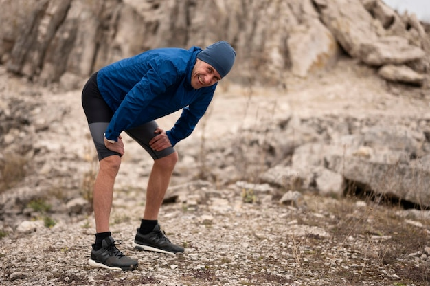 Tiro completo do sexo masculino fazendo uma pausa na trilha na natureza