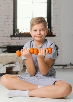 Tiro completo garoto segurando halteres