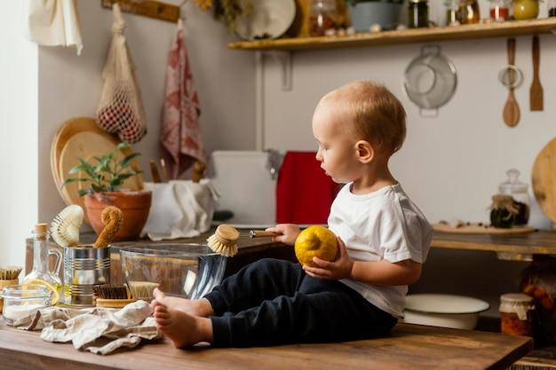 Tiro completo garoto segurando limão e escova