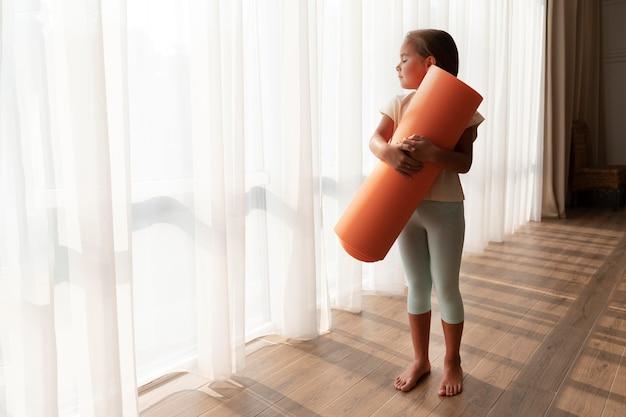 Tiro completo garoto segurando tapete de ioga