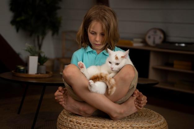 Tiro completo garoto segurando um gato adorável