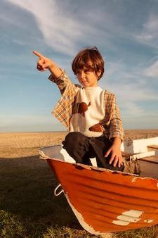 Tiro completo garoto sentado em um barco
