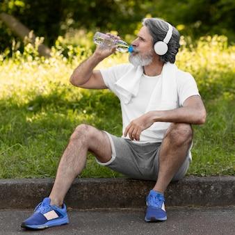 Tiro completo homem bebendo água