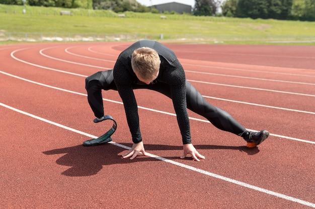 Tiro completo homem com prótese de perna esticando