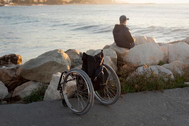 Tiro completo homem deficiente à beira-mar