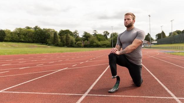 Tiro completo homem deficiente em alongamento em pista de corrida