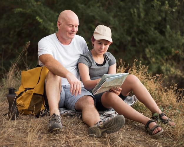 Tiro completo, homem e mulher sentados na grama