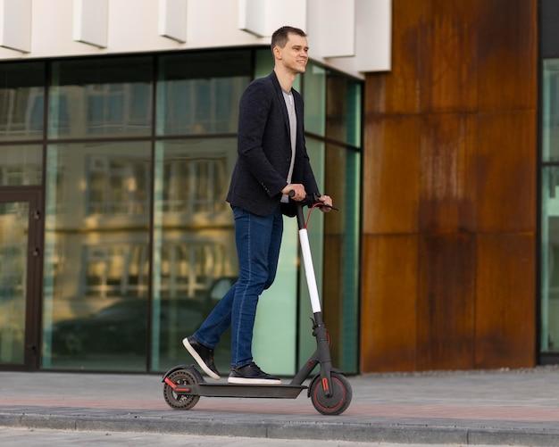 Tiro completo homem em scooter elétrico