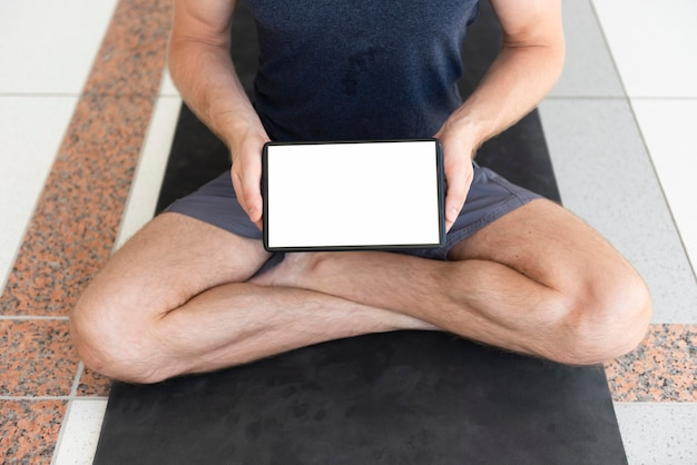 Tiro completo homem em tapete de ioga com tablet em branco