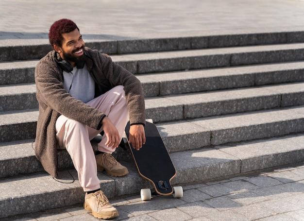 Tiro completo homem na escada com longboard