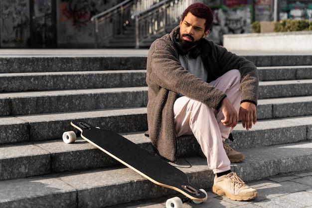 Tiro completo homem posando na escada com longboard