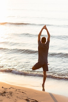 Tiro completo homem praticando pose de árvore em direção ao mar e ao sol
