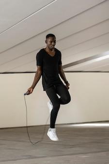 Tiro completo homem pulando corda