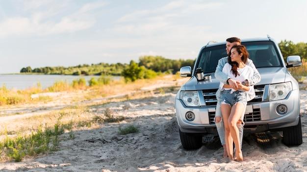 Tiro completo homem segurando mulher perto do carro