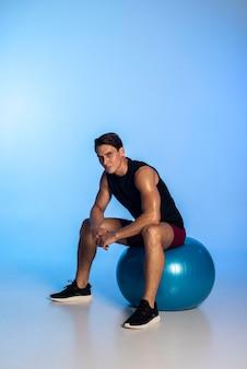 Tiro completo homem sentado na bola de ginástica