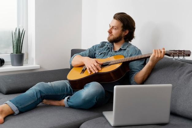 Tiro completo homem tocando violão em casa