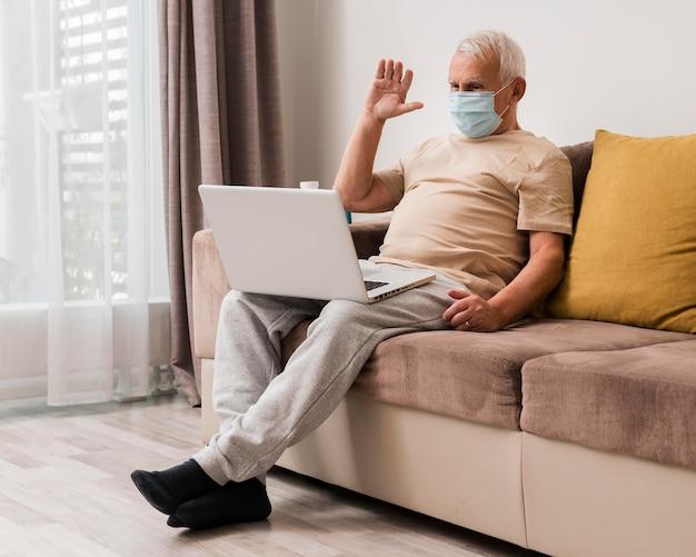 Tiro completo homem usando máscara dentro de casa