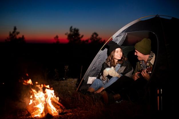 Tiro completo jovem casal se aquecendo à noite