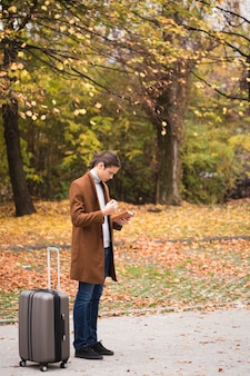 Tiro completo jovem com bagagem no parque