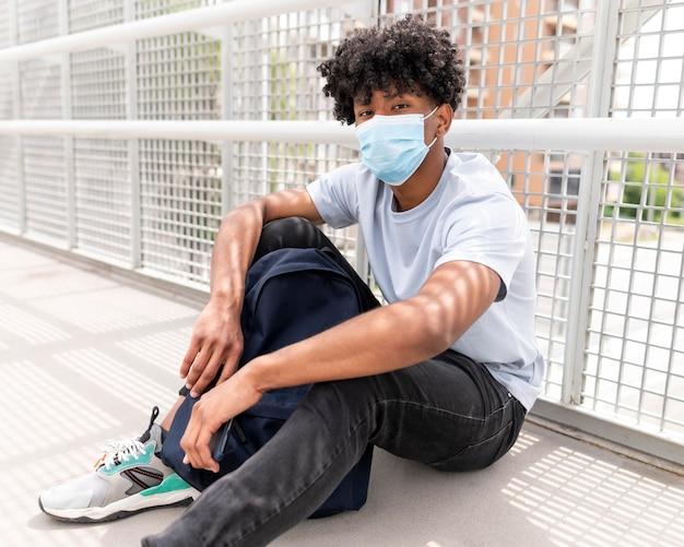 Tiro completo jovem usando máscara facial