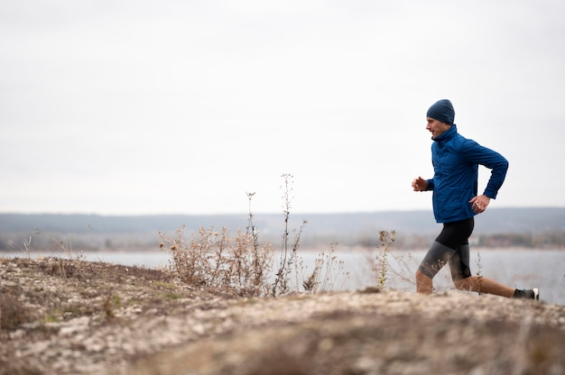 Tiro completo masculino correndo na trilha