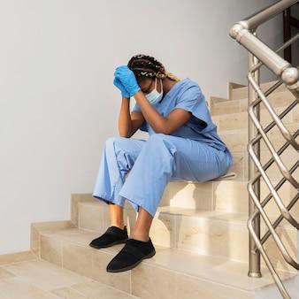 Tiro completo médico sentado na escada