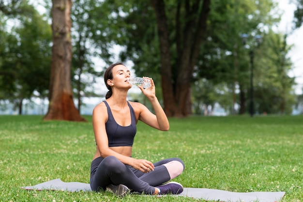 Tiro completo mulher bebendo água ao ar livre
