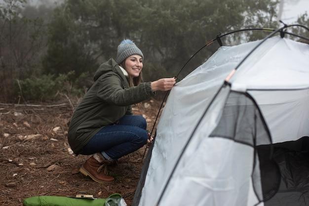 Tiro completo mulher colocando uma barraca