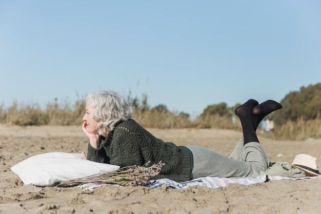 Tiro completo mulher deitada na praia